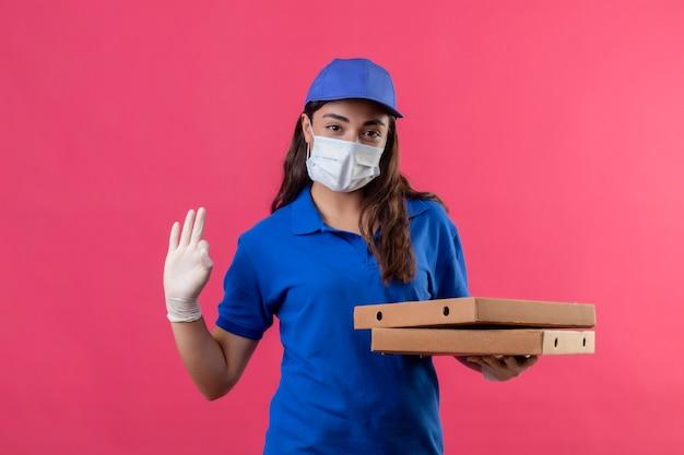 Giovane ragazza delle consegne in uniforme blu e cappuccio che indossa la maschera protettiva per il viso e guanti tenendo le scatole per pizza guardando la telecamera con fiduciosa espressione seria facendo segno ok in piedi su rosa b