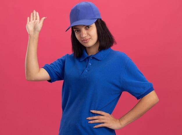 Giovane ragazza di consegna in uniforme blu e cappuccio con espressione fiduciosa che fluttua con la mano che sta sopra la parete rosa