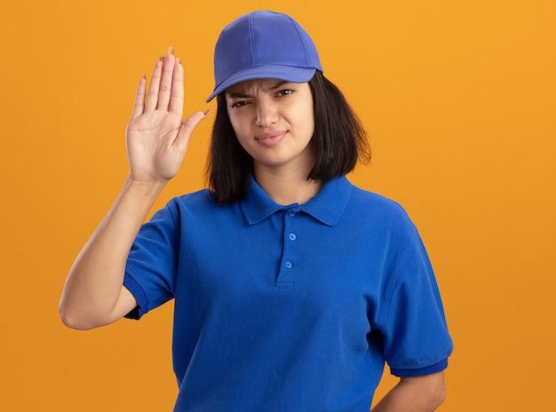 Giovane ragazza delle consegne in uniforme blu e cappuccio con il viso serio che mostra la mano aperta in piedi sopra la parete arancione