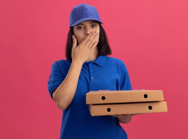 Giovane ragazza di consegna in uniforme blu che tiene le scatole per pizza essendo scioccato che copre la bocca con la mano in piedi sopra la parete rosa