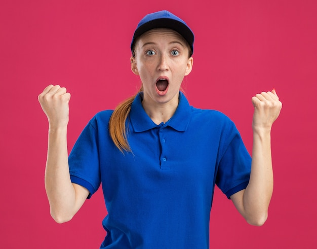 青いユニフォームとキャップの若い配達の女の子は驚いて驚いた握りこぶしを握りしめます