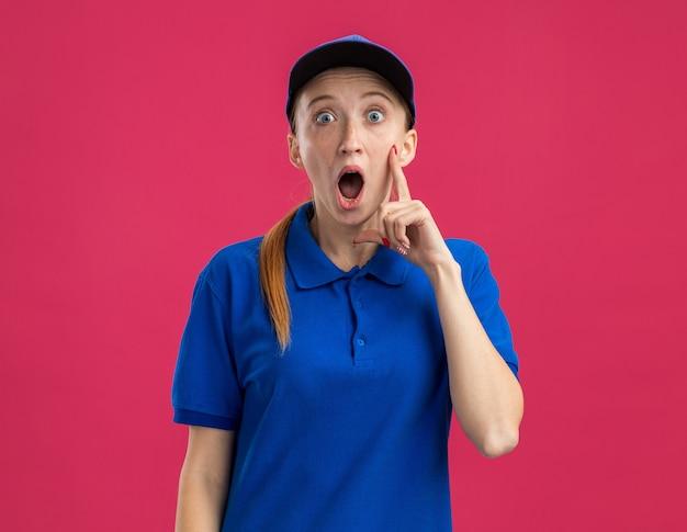 Молодая доставщица в синей форме и кепке изумлена и удивлена, стоя у розовой стены