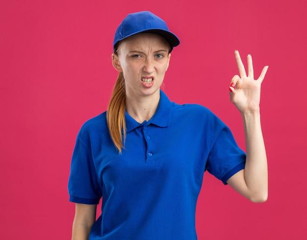 Молодая доставщица в синей форме и кепке недовольна, показывая знак ок, стоящий над розовой стеной