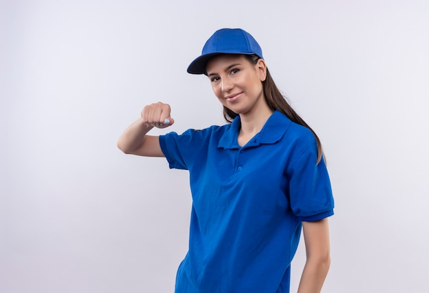 파란색 제복을 입은 젊은 배달 소녀와 친절한 미소를 짓는 인사 제스처를 만드는 주먹 떨림 모자