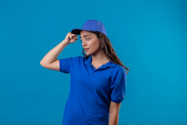 Молодая доставщица в синей униформе и кепке невежественная и смущенная почесывает голову, не имея ответа, стоя на синем фоне