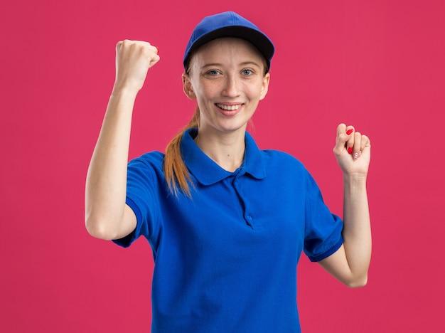 Молодая доставщица в синей униформе и кепке взволнованная и счастливая, сжимая кулаки, стоит над розовой стеной