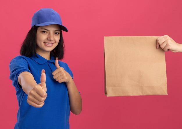 ピンクの壁の上に立って親指を示す紙のパッケージを受け取っている間興奮している青い制服とキャップの若い配達の女の子