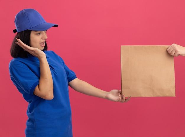 ピンクの壁の上に立っている紙のパッケージを受け取っている間興奮している青い制服とキャップの若い配達の女の子