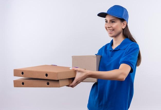 Молодая доставщица в синей форме и кепке дарит покупателю коробки с пиццей, дружелюбно улыбаясь