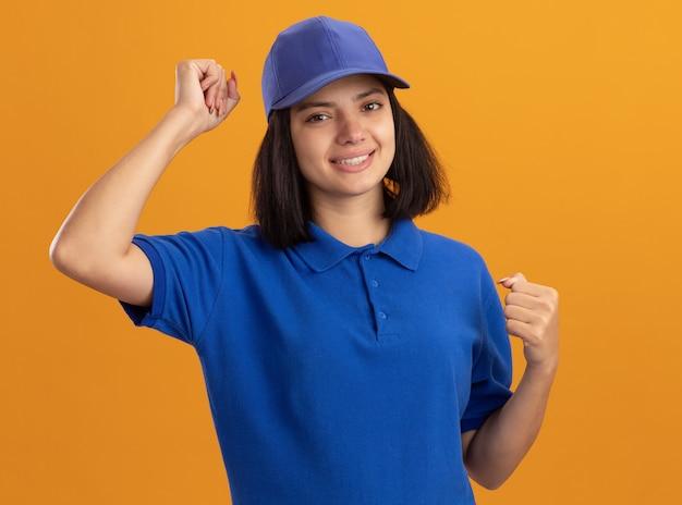 Молодая доставщица в синей форме и кепке счастливая и взволнованная, сжимая кулаки, радуясь своему успеху, стоя у оранжевой стены