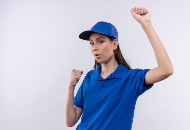 Молодая доставщица в синей форме и кепке счастлива и возбуждена, сжимая кулаки