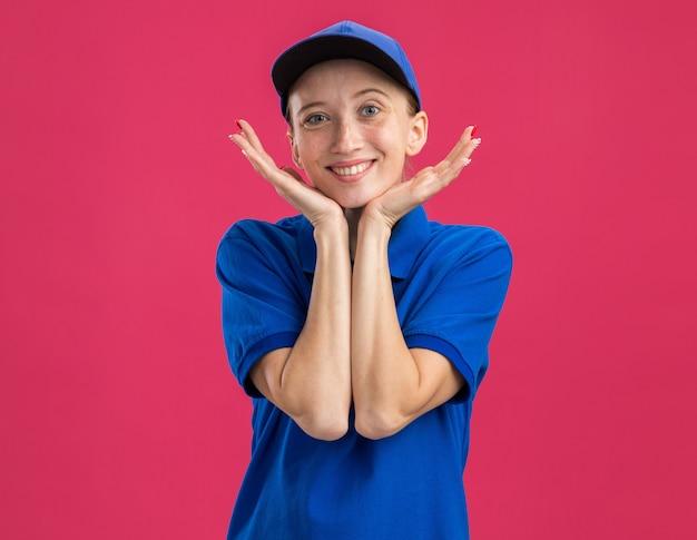 Молодая доставщица в синей форме и кепке счастлива и позитивна, весело улыбаясь, положив руку на лицо