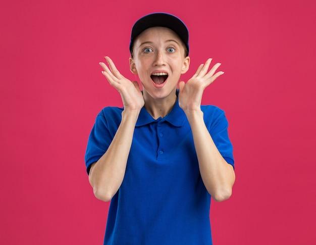 Молодая доставщица в синей форме и кепке счастлива и удивлена с поднятыми руками, стоя над розовой стеной
