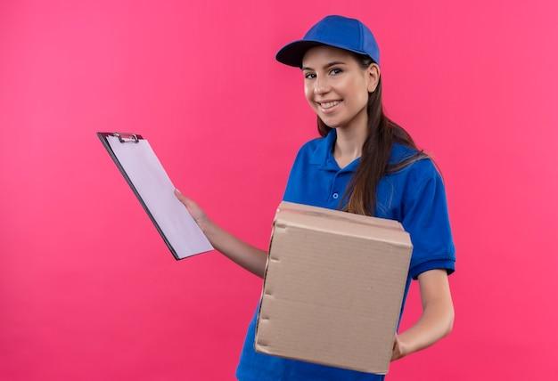 青い制服とキャップ保持ボックスパッケージとクリップボードに自信を持って笑顔に見える若い配達の女の子