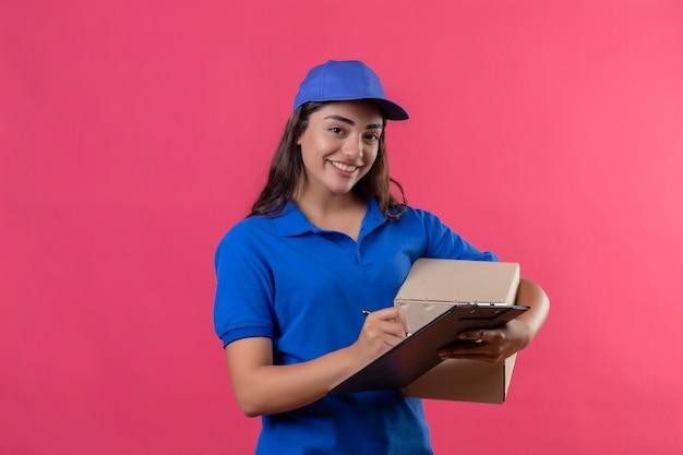 Молодая доставщица в синей форме и кепке, держащая коробку с пакетом и буфер обмена, пишет что-то, глядя в камеру, весело улыбаясь, счастливо и позитивно стоит на розовом фоне