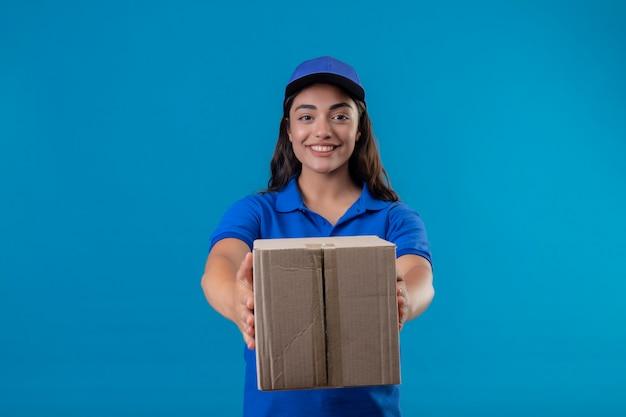 Молодая доставщица в синей униформе и кепке, держащая коробку, дарит ее клиенту, стоящему на синем фоне