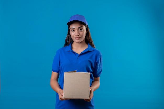 青い背景に自信を持って幸せと肯定的な立っている笑顔カメラを見て青い制服とキャップ保持ボックスパッケージの若い配達の少女
