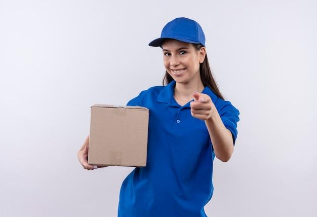 青いユニフォームとキャップ保持ボックスパッケージの若い配達の女の子は、カメラに指で自信を持って指している笑顔