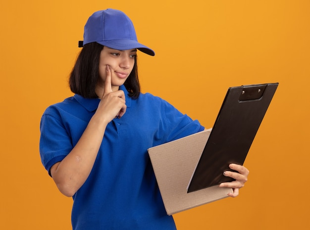 Молодая доставщица в синей форме и кепке держит картонную коробку и буфер обмена, глядя на нее с растерянным выражением лица, стоя над оранжевой стеной