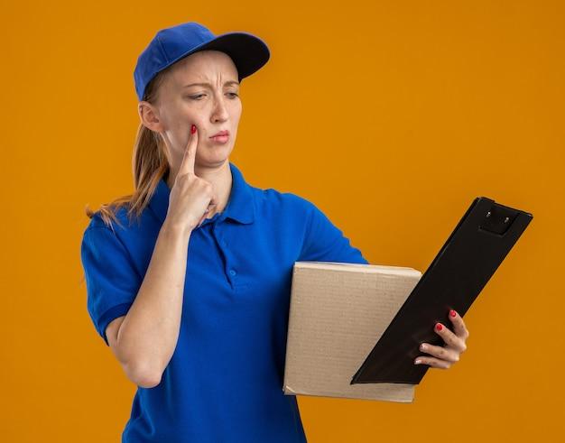Молодая доставщица в синей форме и кепке держит картонную коробку и буфер обмена, глядя на нее с серьезным лицом