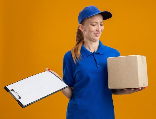 Молодая доставщица в синей форме и кепке держит картонную коробку и буфер обмена, выглядит смущенным и недовольным