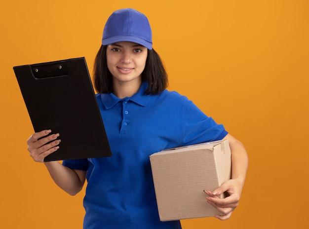 Молодая доставщица в синей форме и кепке держит картонную коробку и буфер обмена, улыбаясь счастливым лицом, улыбаясь, стоя над оранжевой стеной