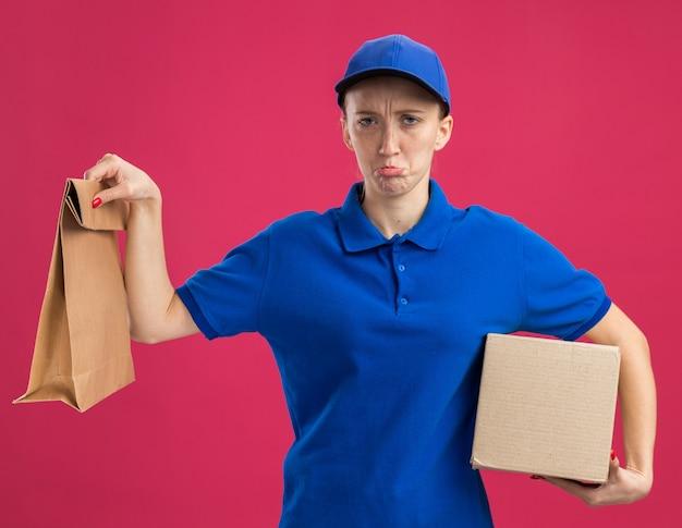 Молодая доставщица в синей форме и кепке держит картонную коробку и бумажный пакет с грустным выражением лица, поджимая губы, стоя над розовой стеной