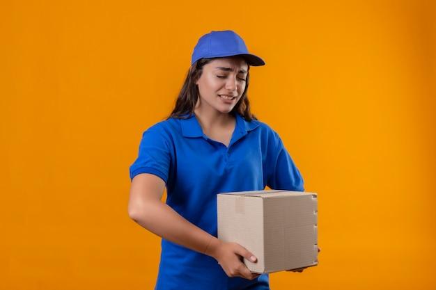 Молодая доставщица в синей форме и кепке держит картонную коробку, глядя в шину и скучающая, стоя на желтом фоне