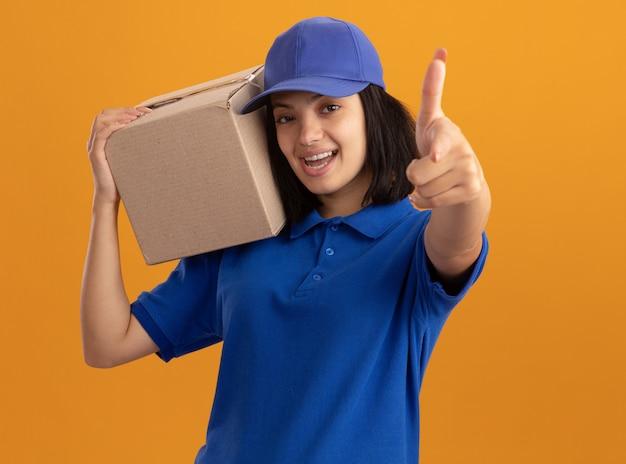 Молодая доставщица в синей форме и кепке держит картонную коробку, весело улыбаясь, указывая указательным пальцем на оранжевую стену