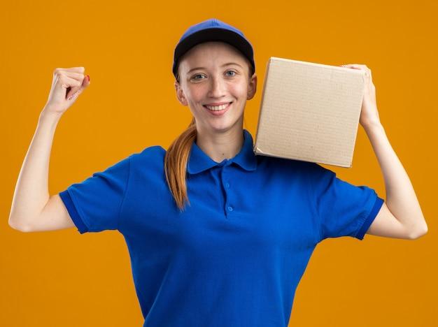 Молодая доставщица в синей форме и кепке держит картонную коробку, улыбаясь, уверенно поднимая кулак, показывая силу