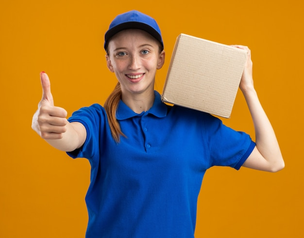Молодая доставщица в синей форме и кепке держит картонную коробку, уверенно улыбаясь, показывает палец вверх