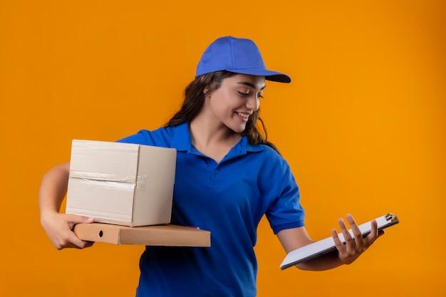 Молодая доставщица в синей форме и кепке держит картонные коробки и буфер обмена, глядя на нее со счастливым лицом, улыбаясь, стоя на желтом фоне