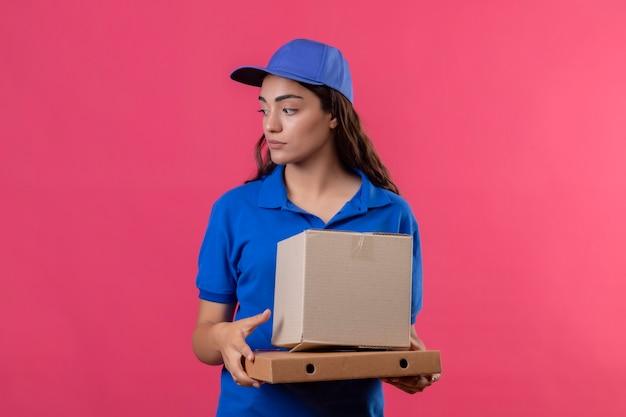Молодая доставщица в синей форме и кепке держит картонные коробки, глядя в сторону с серьезным уверенным выражением лица, стоящего на розовом фоне