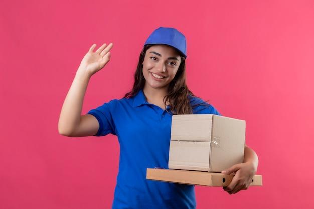 Молодая доставщица в синей форме и кепке держит картонные коробки, глядя в камеру, улыбаясь дружелюбно машет рукой, стоя на розовом фоне