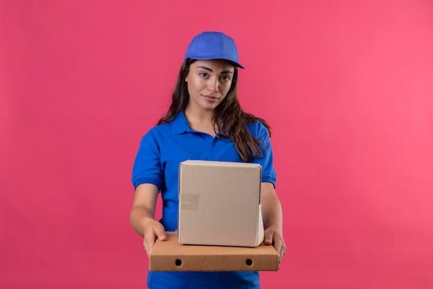 Молодая доставщица в синей форме и кепке держит картонные коробки, глядя в камеру с серьезным уверенным выражением лица, стоящим на розовом фоне