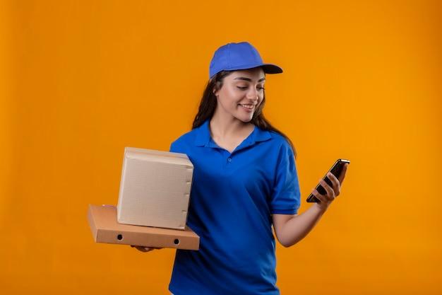 Молодая доставщица в синей форме и кепке держит картонные коробки, глядя на экран смартфона, уверенно улыбаясь, стоя на желтом фоне