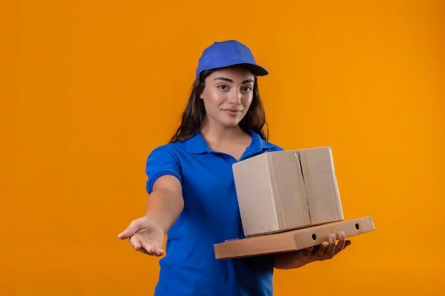 Молодая доставщица в синей форме и кепке держит картонные коробки, выглядит уверенно, делая приветственный жест рукой, стоя на желтом фоне
