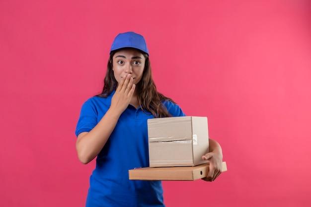 Молодая доставщица в синей форме и кепке держит картонные коробки с удивленным и изумленным видом, прикрывая рот рукой, стоящей на розовом фоне
