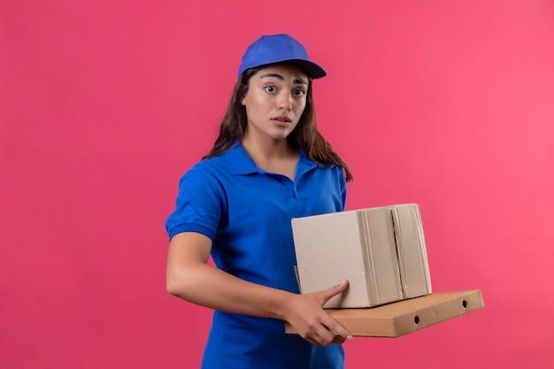 Молодая доставщица в синей форме и кепке держит картонные коробки, выглядя удивленными и удивленными, стоя на розовом фоне