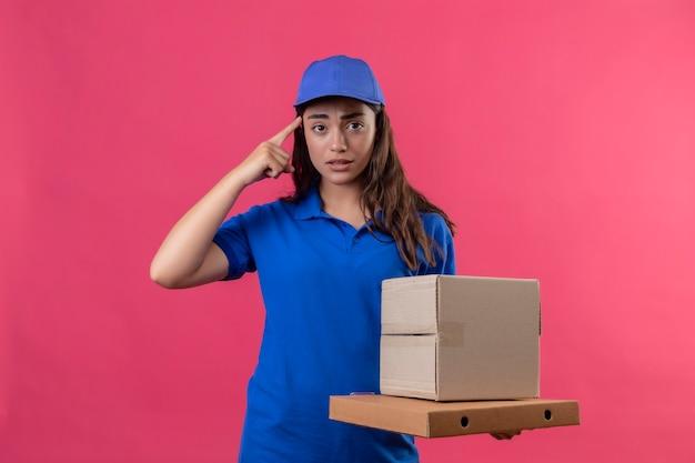 Молодая доставщица в синей форме и кепке держит картонные коробки, указывая на храм за ошибку, выглядит встревоженной, стоя на розовом фоне