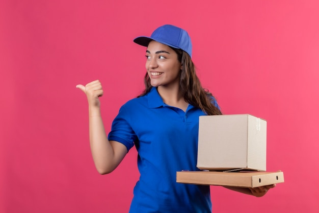 Молодая доставщица в синей форме и кепке держит картонные коробки, указывая пальцем в сторону, весело улыбаясь и весело глядя в сторону, стоя на розовом фоне
