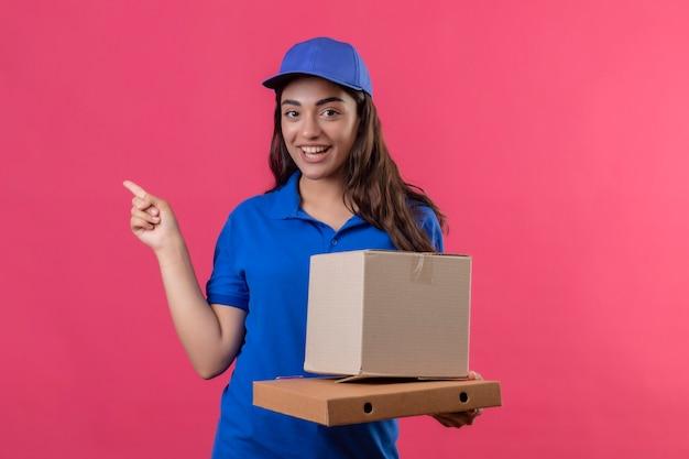 Молодая доставщица в синей форме и кепке держит картонные коробки, указывая пальцем в сторону, весело улыбаясь и радостно улыбаясь, стоя на розовом фоне