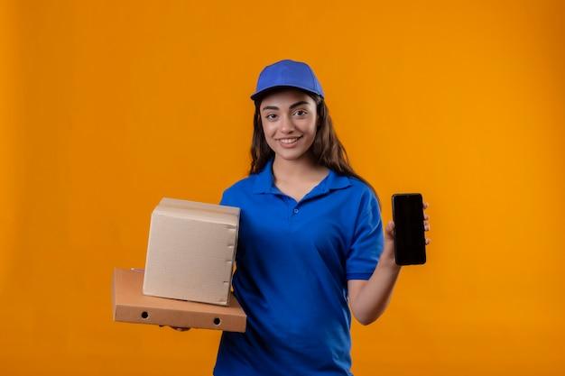 Молодая доставщица в синей форме и кепке держит картонные коробки, показывая смартфон, уверенно улыбаясь, стоя на желтом фоне