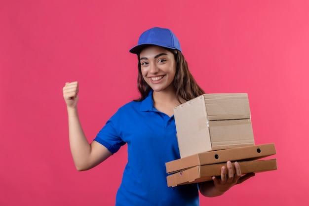 Молодая доставщица в синей форме и кепке держит картонные коробки, весело улыбаясь, поднимая кулак, радуясь своему успеху и победе, стоя на розовом фоне