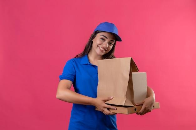 Молодая доставщица в синей форме и кепке держит картонные коробки, весело улыбаясь, стоя на розовом фоне