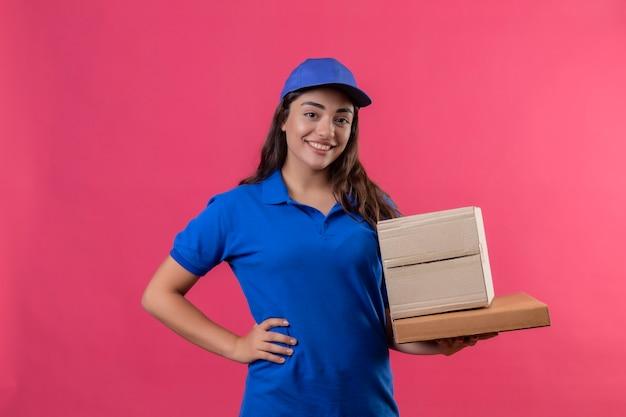 Молодая доставщица в синей форме и кепке держит картонные коробки, улыбаясь уверенно позитивно и счастливо стоя на розовом фоне