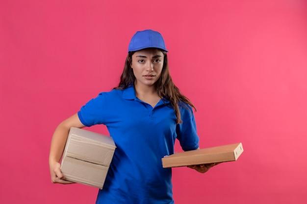 Молодая доставщица в синей форме и кепке держит картонные коробки, стоя с грустным выражением лица на розовом фоне