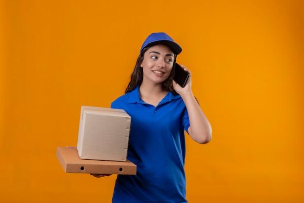 Молодая доставщица в синей форме и кепке держит картонные коробки, разговаривает по мобильному телефону и выглядит уверенно, стоя на желтом фоне