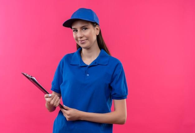 파란색 제복을 입은 젊은 배달 소녀와 얼굴에 자신감이있는 미소로 카메라를보고 클립 보드를 들고 모자