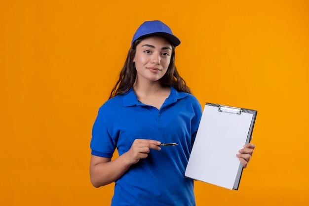 Молодая доставщица в синей форме и кепке держит буфер обмена, указывая ручкой, глядя в камеру, уверенно улыбаясь, стоя на желтом фоне